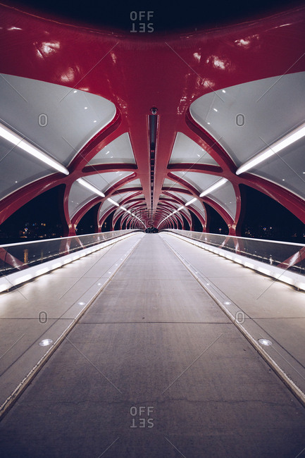 Perspective view of modern construction of pedestrian bridge illuminated in dark night, Canada