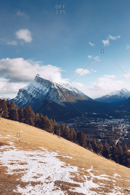 Hill with yellow frozen soil and thick forest on background with snowy mountains and blue sky with few clouds and valley with small city