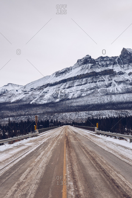 Fenced bridge with signboards passing through thick winter woods and frozen river on snowy mountain background with cloudy grey sky
