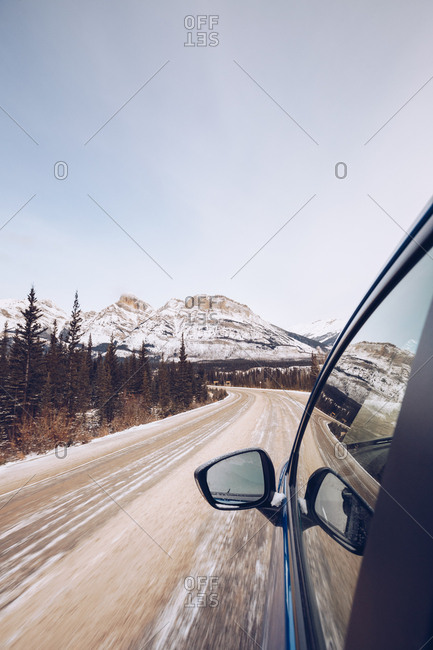 Clean pickup with people driving on Canadian forest road with many firs and on background with snowy mountains and cloudy sky