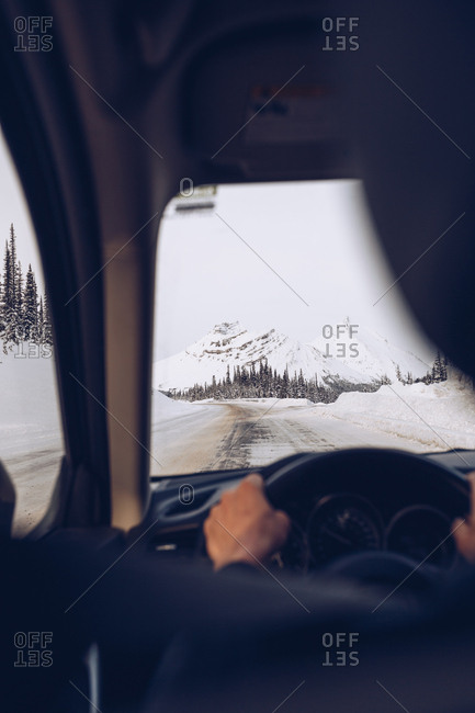 Male holding helm in dark interior and driving vehicle on road passing through forest on white snowy Canadian mountains background in soft focus