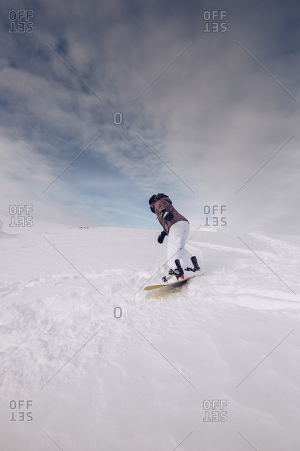 Unrecognizable female wearing warm clothes and snowboard with special ammunition gliding downhill? on cloudy sky background