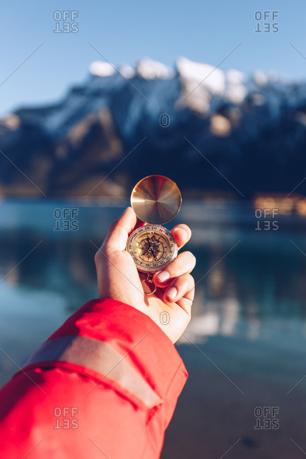 Human dressed in red jacket holding golden compass in sunny day on blurred Canadian mountains background