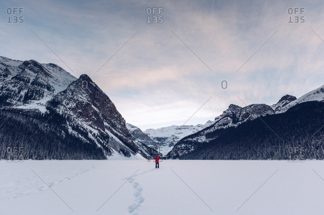 View at distance of anonymous traveler standing in spacious cold snowy field with rocky dark mountains on background