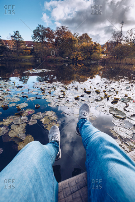 Crop legs above water in autumnal park