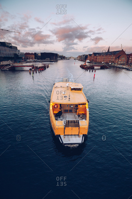 September 11, 2018: View of orange colored ship sailing on calm water of city channel in dusk, Denmark