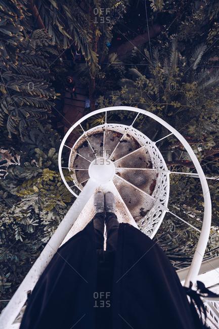 September 11, 2018: Crop legs of person on white shabby spiral stairway above lush green vegetation of park, Denmark
