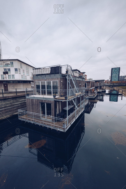 Contemporary residential house on water of city channel reflecting sky, Denmark