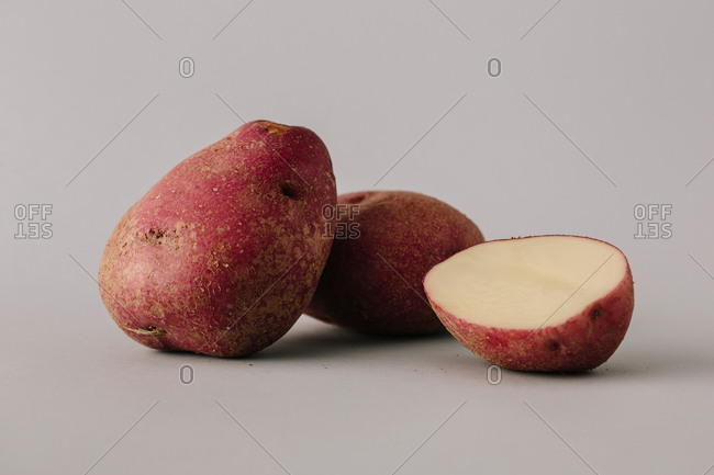 Whole and cut potatoes lying in pile on�gray background