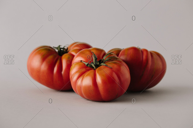 Pile of fresh seasonal ripe tomatoes with green leaves composed on�gray background