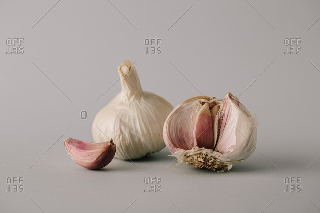 Close-up shot of few cloves and heads of ripe fresh garlic on gray background