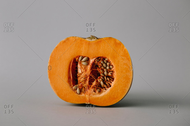 Juicy fresh half of rope bright orange pumpkin with seeds and flesh