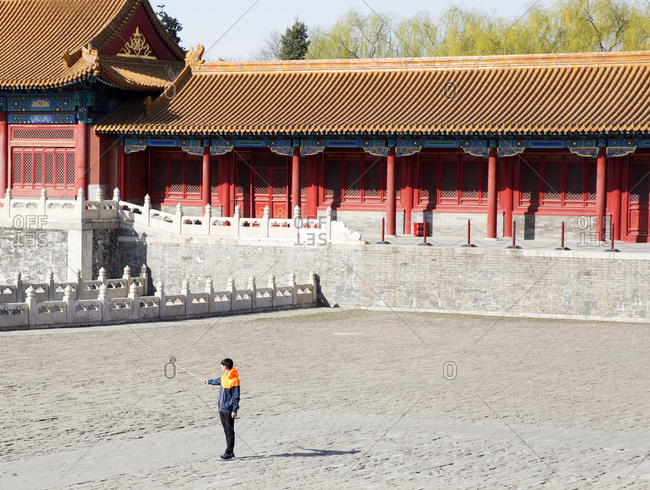 Beijing, China - March 22, 2016: Tourist taking a selfie with a selfie stick at the Forbidden City palace complex