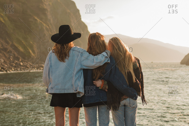 Three friends embraced observing sunset in a day of summer islands background