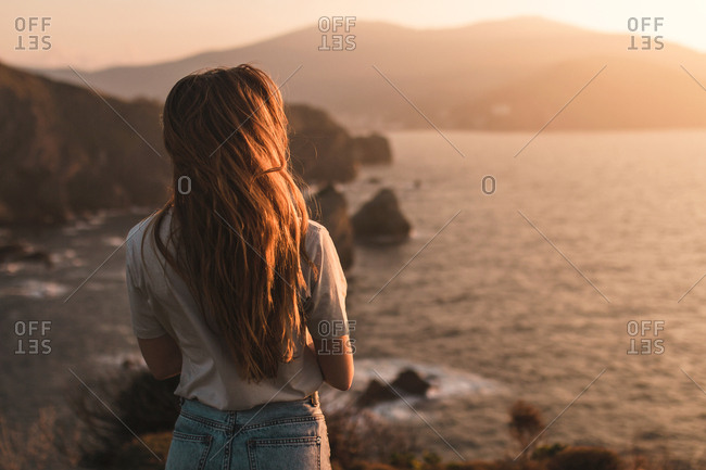 Rear view of young blond girl observing the horizon in a sunset of summer islands and sea background