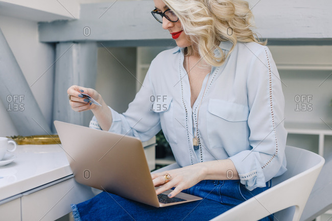 Beautiful Caucasian woman holding credit card for online payment and typing on her laptop
