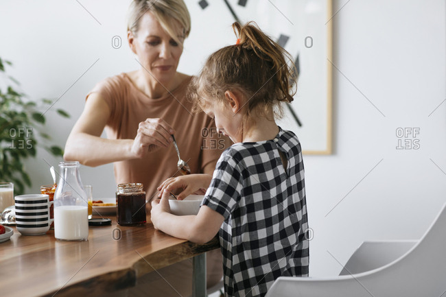 Mother making breakfast for her cute daughter