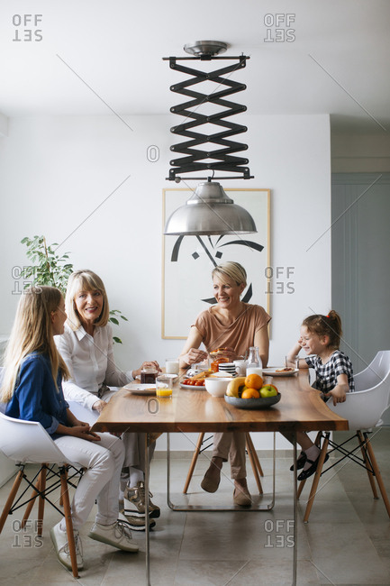 Pretty Caucasian woman having breakfast with her mother and daughters