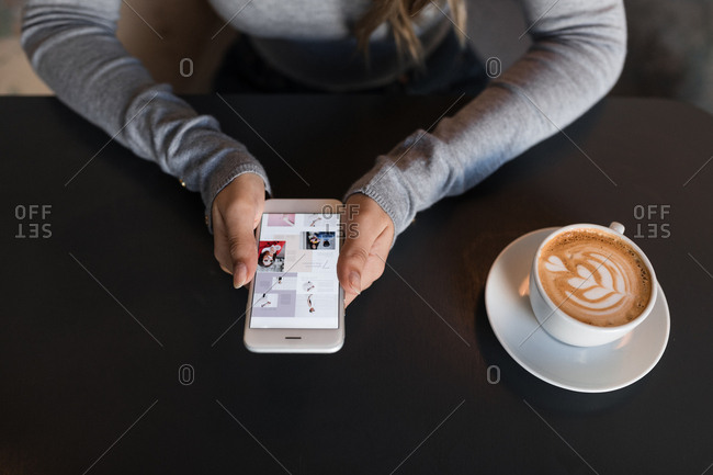 Hands of unrecognizable  woman using her cell phone at cafe