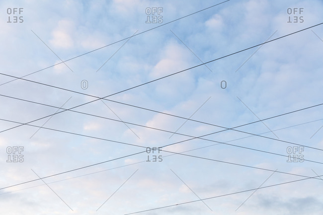 Intersecting power lines in front of cloudy background