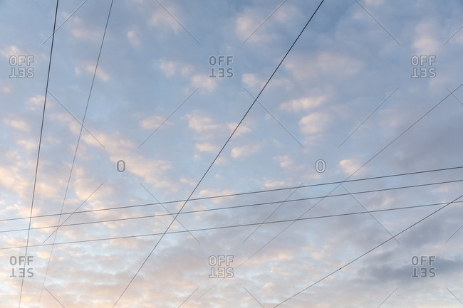 Intersecting power lines in front of cloudy background in the evening