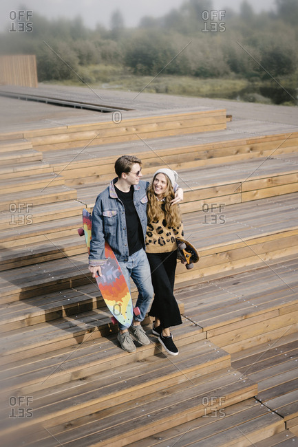 Young handsome man hugging woman with longboard in hand