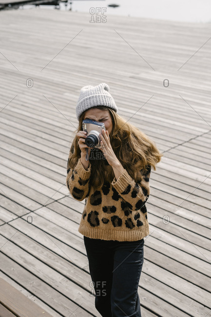 A woman in a leopard sweatshirt makes a photo on an instant camera