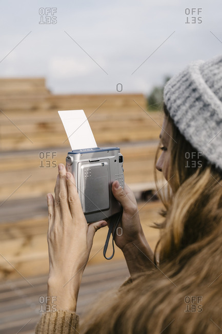 A woman in a hat makes a photo on an instant camera
