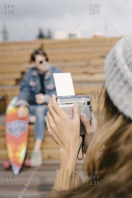 A woman is taking a photo on an instant camera of a man with a long board