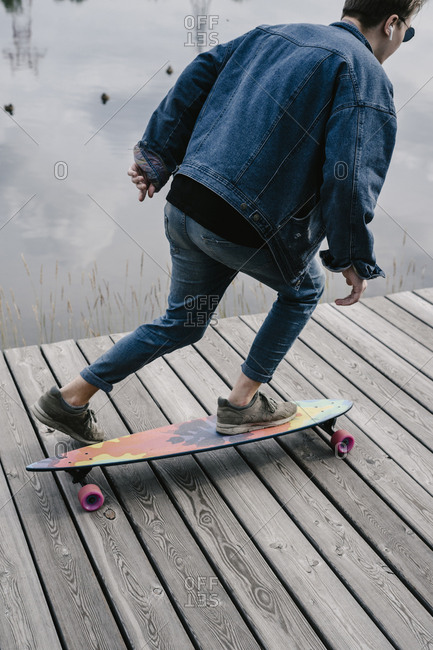 A handsome man in a jeans is riding a longboard on the waterfront