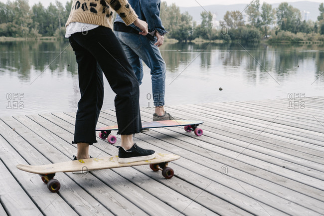 A woman in a leopard jacket and a man riding a longboard along the river
