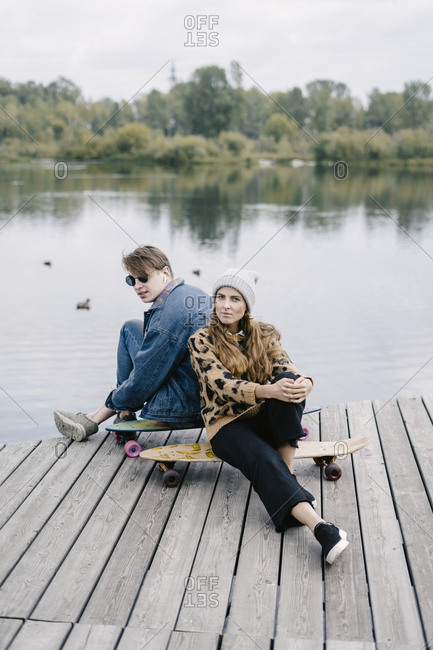A woman in a leopard jacket and a man are sitting on longboards by the river
