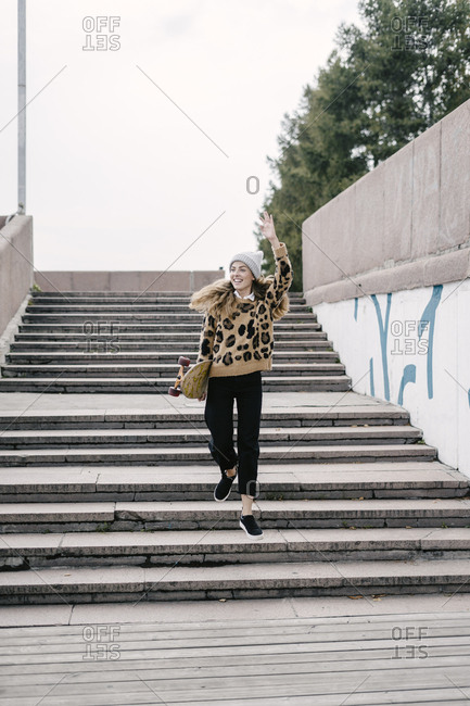 Beautiful woman in a leopard sweater and hat goes down the concrete steps