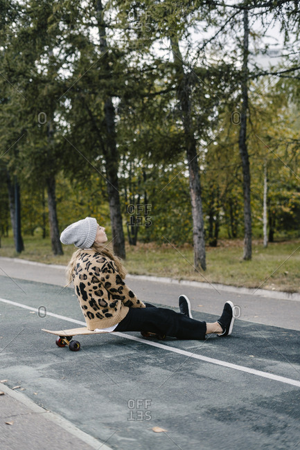 Beautiful woman in a leopard sweatshirt resting while sitting on a longboard on the road