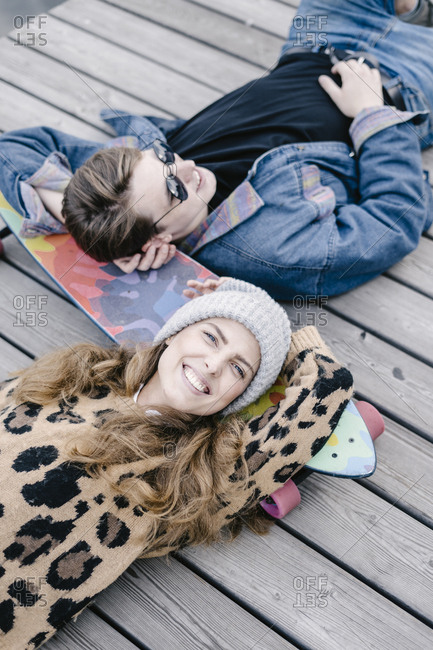 A woman in a leopard jacket is lying on a longboard with a handsome man in round sunglasses and smile
