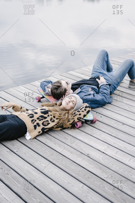 A woman in a leopard jacket is lying on a longboard with a handsome man in round sunglasses