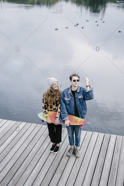 A woman in a leopard jacket is standing and is holding a longboard next to a handsome man in round sunglasses