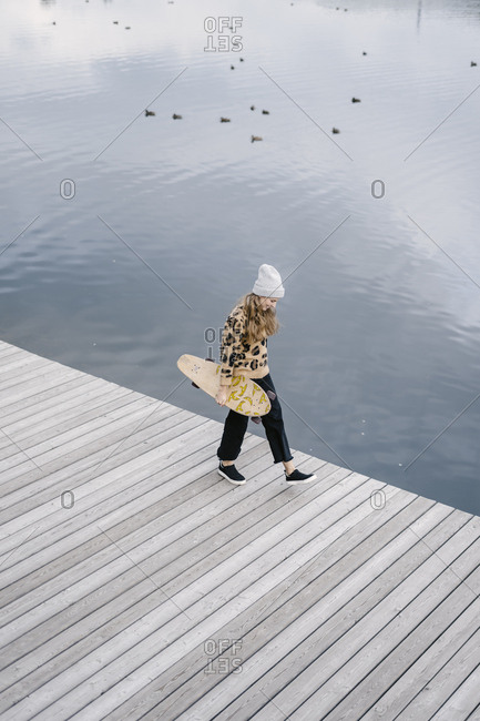 A woman in a leopard jacket walks along the pier with a longboard in her hand