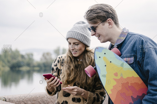 A woman in a leopard jacket is holding a smartphone and watching a photo of a selfie with a handsome man in round sunglasses
