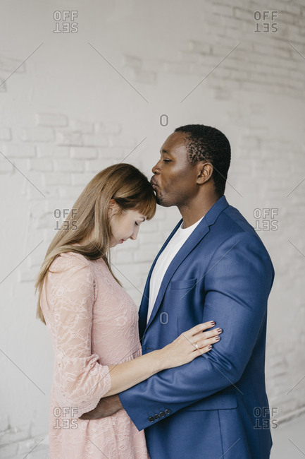 The husband kisses his wife on the forehead very gently and romantically