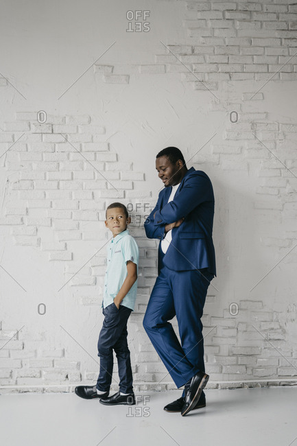 Father and son are standing near the white brick wall and looking at the camera