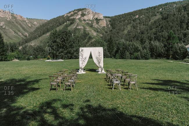 Wedding ceremony with a square arch and wooden chairs. rustic wedding in nature. mountain and forest view