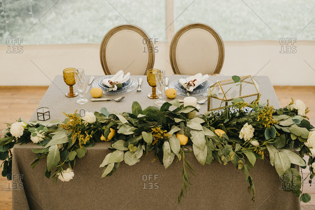 Wedding table for the groom and the bride. italian wedding decor. rustic style with lemons. served table with plates and glasses