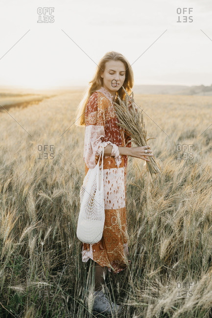 Young woman in a boho chic dress standing in a field with wheat at sunset. with a can of milk