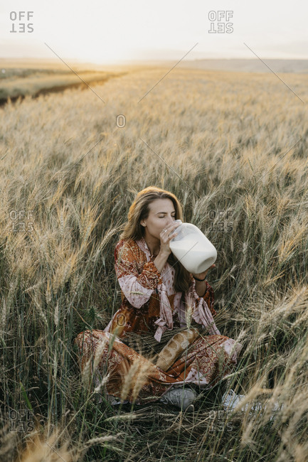 Beautiful young woman in a boho chic dress sitting in a field with wheat at sunset. and drinks milk from a can