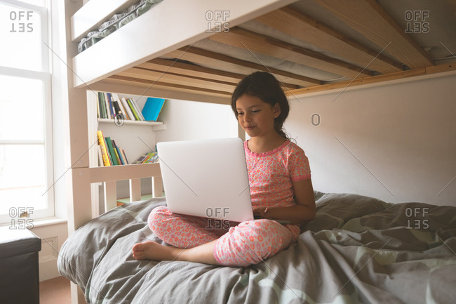 Young girl using laptop on bed in bedroom at home