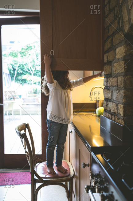 Girl searching for food in kitchen at home