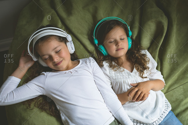 Siblings listening music while relaxing in bedroom at home