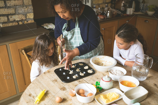 Grandmother with her granddaughters preparing breakfast on dining table at home