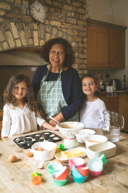 Grandmother standing with her granddaughters in kitchen at home